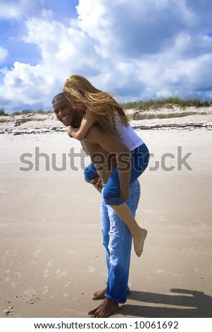 Man carrying woman on his back on a beach.