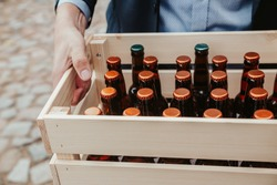 Man carrying wooden crate full of unmarked beverage bottles.