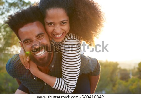 Man carrying young woman on his shoulders, looking to camera #560410849