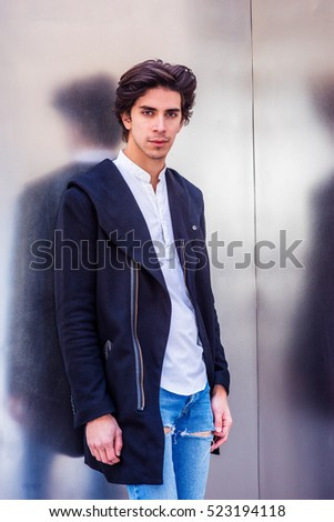 Man Casual Fashion. Portrait of American college student in New York. Young handsome man wearing fashionable long coat, jeans, standing against metal wall, looking at you. Filtered with purple tint.