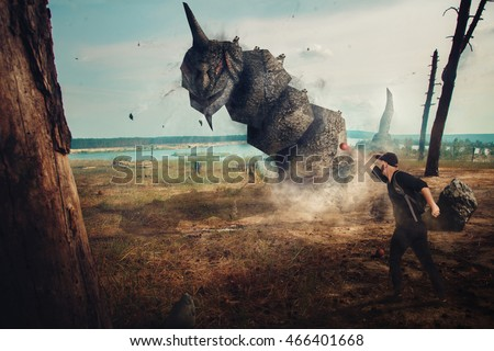 Stock Photo Man catching a stone monster in real life outdoors. creative photo of real monster. monster in real life.