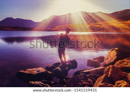 Man Catching Fish While Fishing In Mountain Lake At Beautiful Sunset In Autumn	  #1541559431