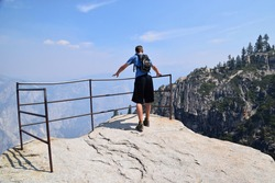 Man cautiously walks towards metal railing on the edge of mountain in Yosemite National Park.