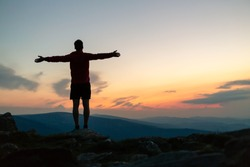 Man celebrating sunset on mountain top. Looking at inspiring view. Trail runner, hiker or climber reached mountain peak, enjoy inspirational landscape on rocky trail Karkonosze, Poland