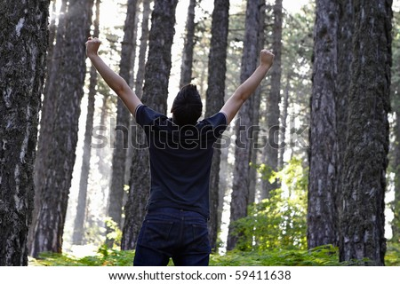 Man celebrating with arms lifted in the forest