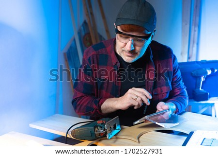 Man changes the nozzle for a jig saw. Parquet cutting. Concept - work with a dangerous tool. The furniture maker. Furniture manufacturing. Joiner next to jig saw. Man in safety glasses. A carpenter
