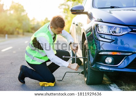 man changes wheels on a car. unscrews the wheel nuts with a wrench. car service. lifts the car with a jack Foto stock ©