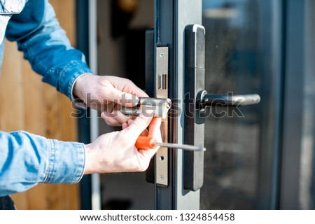 Man changing core of a door lock of the entrance glass door, close-up view with no face