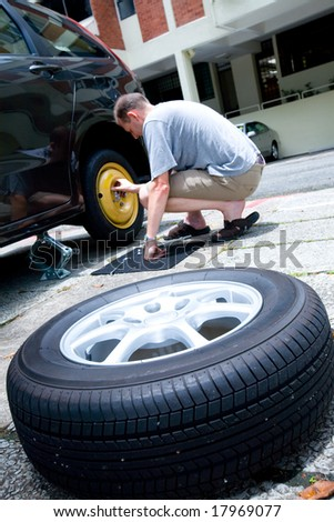 Man changing his tire as he suffers from a puncture - stock photo