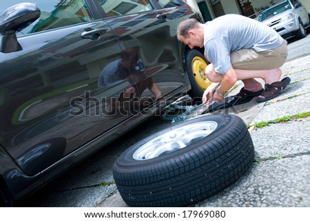 Man changing his tire as he suffers from a puncture
