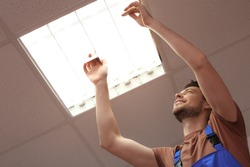 Man changing light bulb in lamp, indoors