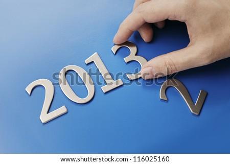 Man changing metallic numbers to year 2013.