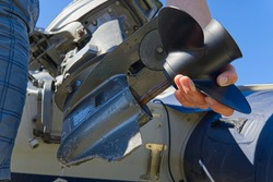man changing propeller on outboard motor. Repairing outboard motor for boat, replacing screw.