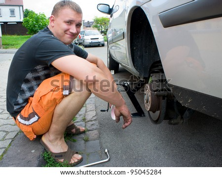 Man changing the car wheel on the road