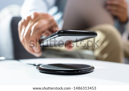 Man Charging Smartphone Using Wireless Charging Pad At Home Stockfoto ©