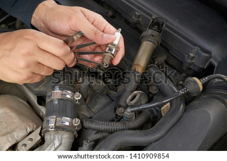 man check spark gap in the ignition plug with blade feeler gauge Stockfoto ©