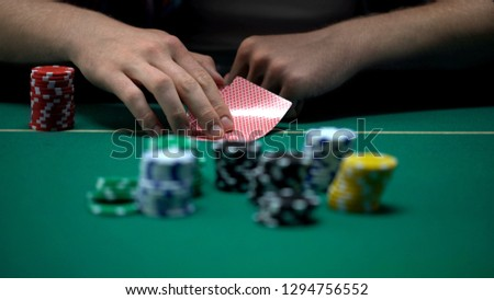 Man checking cards and raising, bluffing during poker tournament, chance to win #1294756552