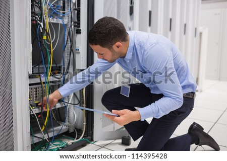 Man checking tablet pc as he is plugging cables into server in data center Stock photo ©