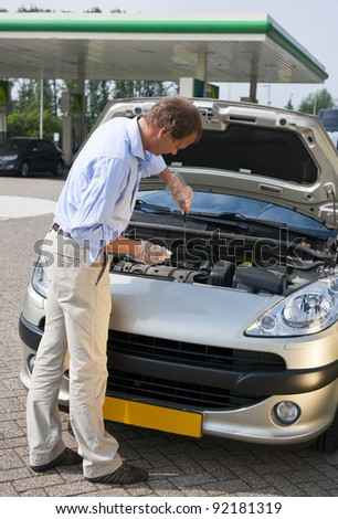 Man, checking the oil level of the engine of his car at a gas station