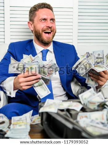 Man cheerful happy businessman with pile dollar banknotes. Profit and richness concept. Businessman formal suit hold cash dollars hands. Che k out my profit this month. Earn money easy business tips. Stock foto ©