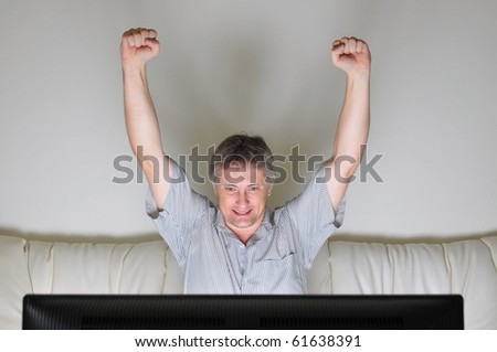 Man cheering whilst watching a television or computer screen