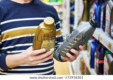 Man choices engine oil in the supermarket