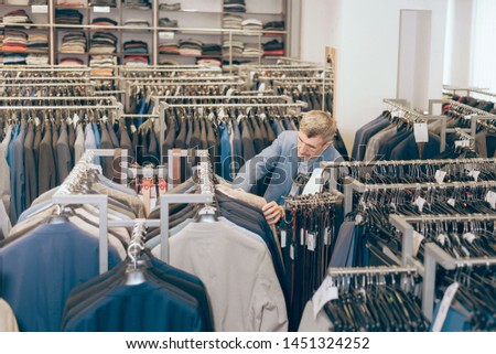 man chooses clothes in a boutique. the store has a lot of jackets, belts. buying and choosing new clothes. #1451324252