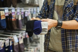 Man chooses socks at the store. Man holds black, blue, gray socks in his hands