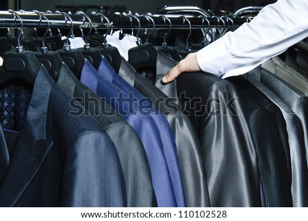 Man choosing business jacket from the raw in the shop.