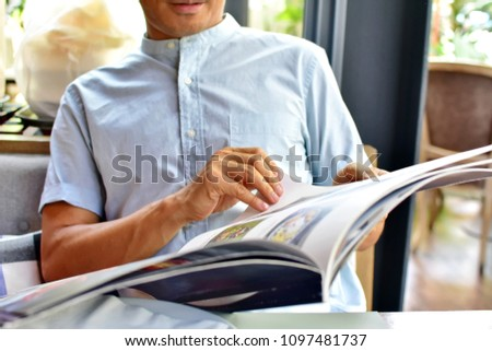 Man choosing food menu in restaurant, hand touching big size of menu book, selective focus blurred background, enjoying with Thai food concept