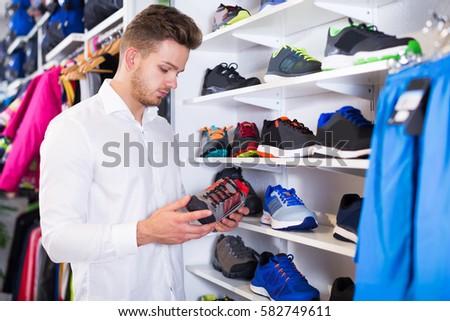 Man choosing new sneakers in sports store