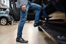 Man choosing pickup truck in car dealership