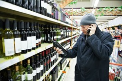 man choosing produces in vegetableduring weekly shopping at supermarket store