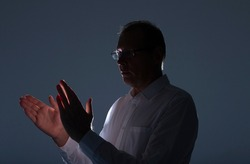 Man clapping hands in white shirt with backlit. Male hands apllauding. Applause.