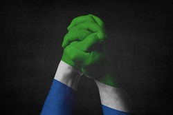 Man clasped hands patterned with the SIERRA LEONE flag.Black background