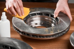 Man cleaning a brake rotor from rust, using a fabric cloth and anti rust spray. Rustproof treatment for car parts.
