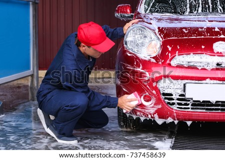 Man cleaning automobile with sponge at car wash #737458639