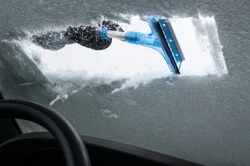 Man Cleaning Car Windshield From Snow and Ice