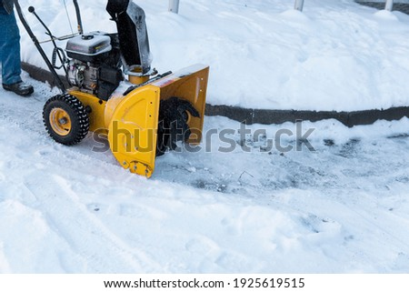 Man cleaning driveway with snow machines after a snow storm. Snow removal equipment working on the street. Cleaning of streets from snow. It's snowing.