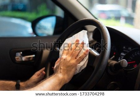 Man cleaning his car steering wheel for disinfection and a safe ride during the virus pandemic closeup