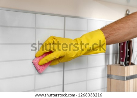 Man cleaning kitchen wall tiles with sponge, closeup #1268038216