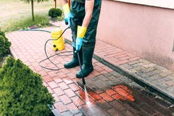 Man cleaning red, conrete pavement block using high pressure water cleaner. Paving cleaning concept. Man wearing waders, protective, waterproof trousers and gloves doing spring jobs in the garden.