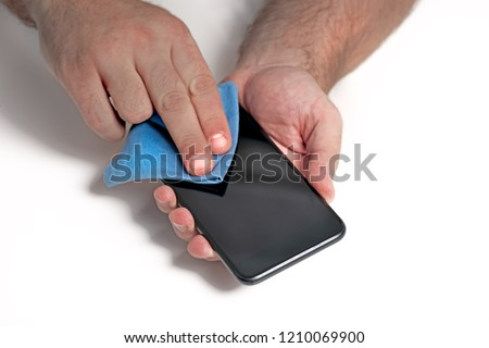 Man cleaning smartphone screen with cloth before applying screen protector.