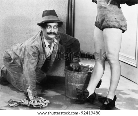 Man cleaning the floor looking at the legs of a woman