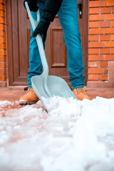 Man Cleaning the snow with plastic shovel. Close up Snow shoveling in front of the brick House on winter day