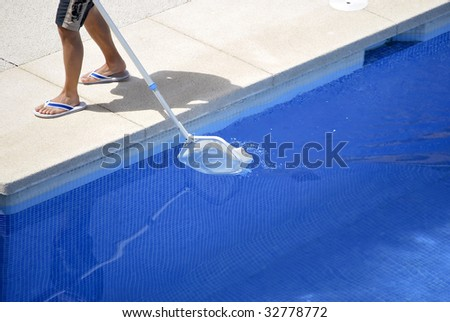Man cleaning the swimming pool. Summer work