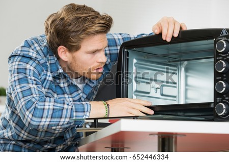 man cleaning up after replacing the filter in a microwave #652446334