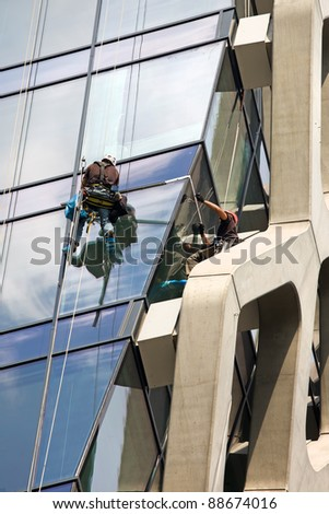 Man cleaning windows of a modern office building