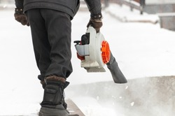 Man cleans pavement from snow with blower