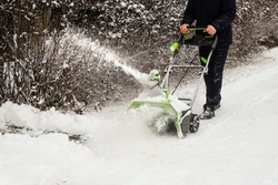 Man cleans snow off path with wireless electric snow blower